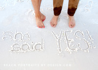 couples feet and engagement written in the sand!