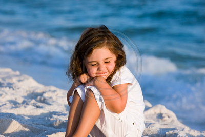 little girl hugging herself on the beach in the sand